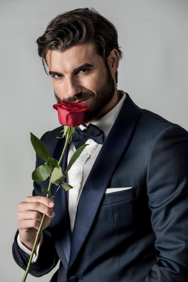 Andi Constantin, într-un costum albastru și un trandafir roșu în mână