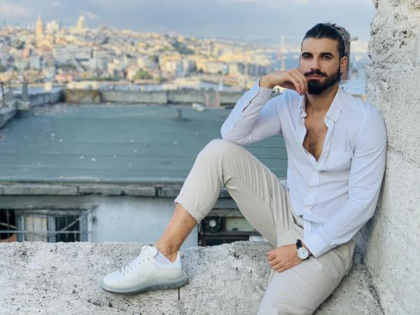 Andi Constantin, în cămașă albă și pantaloni crem, stă pe un zid