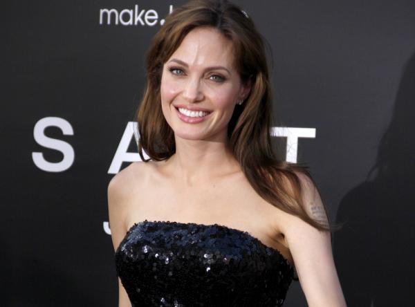 Angelia Jolie, îmbrăcată într-o rochie neagră, cu umerii goi, zâmbește la camera foto