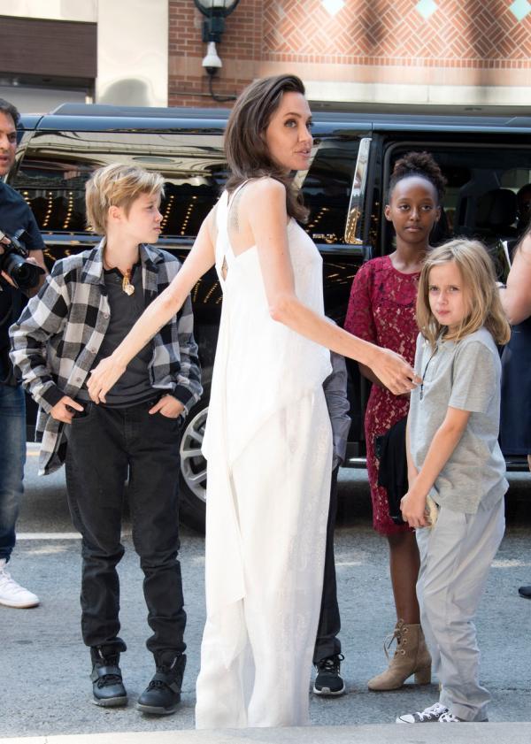 Angelina Jolie, îmbrăcată într-o rochie lungă, albă, împreună cu trei dintre copii