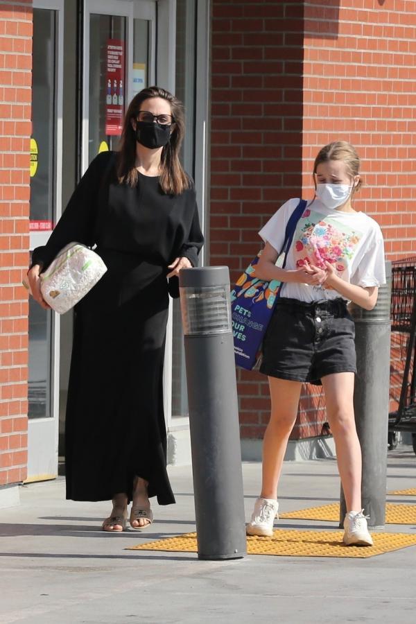 Angelina Jolie, îmbrăcată într-o rochie lungă, neagră, împreună cu una dintre fiice, pe stradă