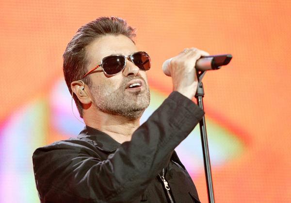 George Michael, îmbrăcat în negru, cu ochelari la ochi, cântă la microfon