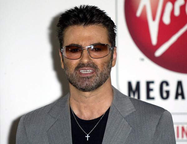 George Michael, îmbrăcat în sacou gri cu o bluză neagră pe dedesubt, și ochelari