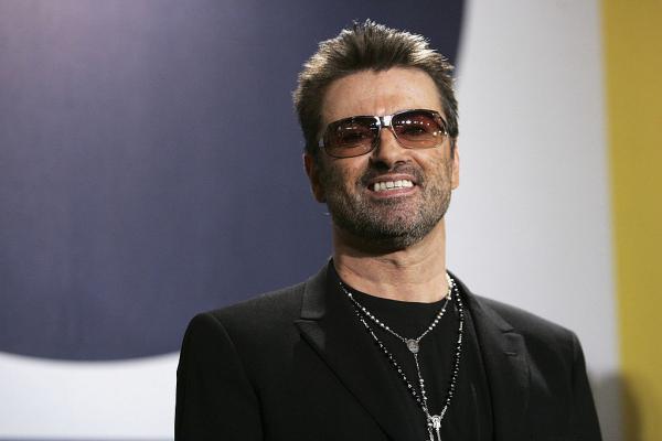 George Michael, îmbrăcat în negru, cu ochelari la ochi, zâmbind
