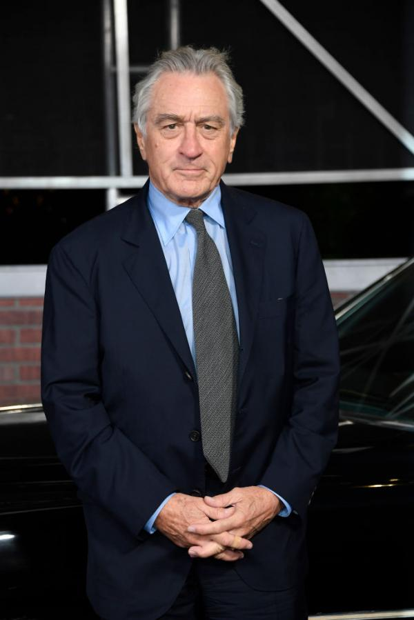 Robert De Niro într-un costum negru și cămașă albastră, iar cravata gri