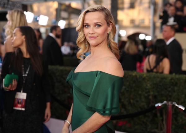 Reese Witherspoon îmbrăcată într-o rochie verde, cu părul desfăcut, privește zâmbind la cameră