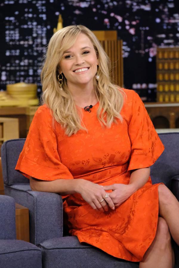 Reese Witherspoon îmbrăcată într-o rochie portocalie, cu părul desfăcut, râde