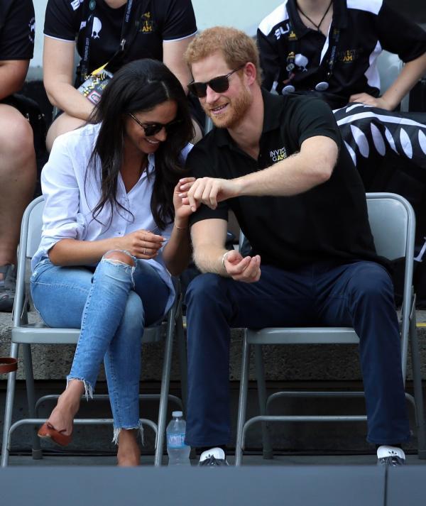 Prințul Harry și Meghan Markle stau pe scaune, unul lângă altul, îmbrăcați casual