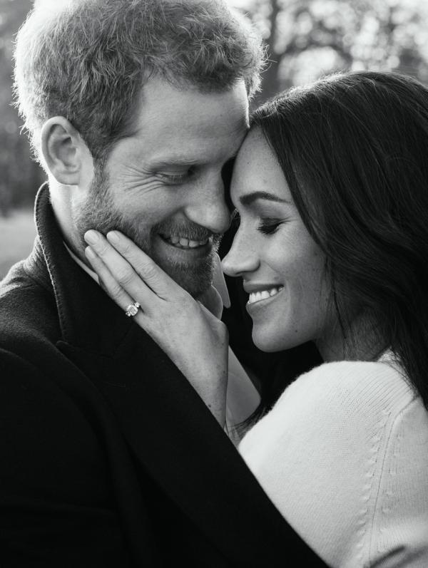 Prințul Harry și Meghan Markle stau îmbrățișați și zâmbesc, fotografie alb negru