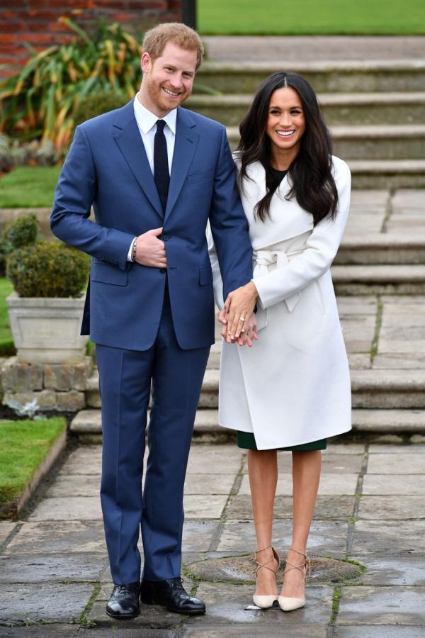 Prințul Harry și Meghan Markle, îmbrăcați elegant. El este într-un costum albastru, ea în rochie și palton deschis la culoare