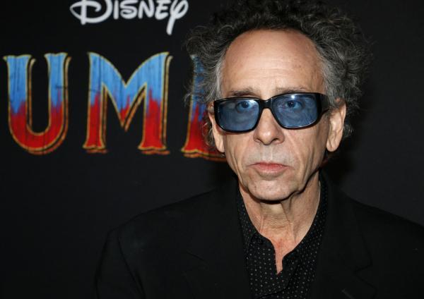 Tim Burton este îmbrăcat în negru, are ochelari la ochi