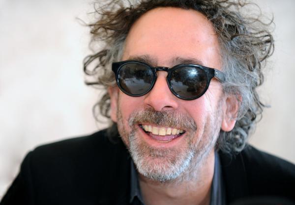 Tim Burton zâmbește, are ochelari de soare și este îmbrăcat în negru
