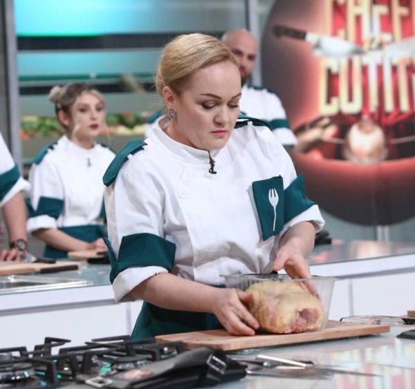 Victorina Mateveev în tunică albă și verde, gătește
