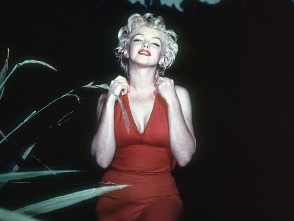 Marilyn Monroe, zâmbitoare, îmbrăcată într-o rochie roșie, își ine mâinile în preajma gâtului