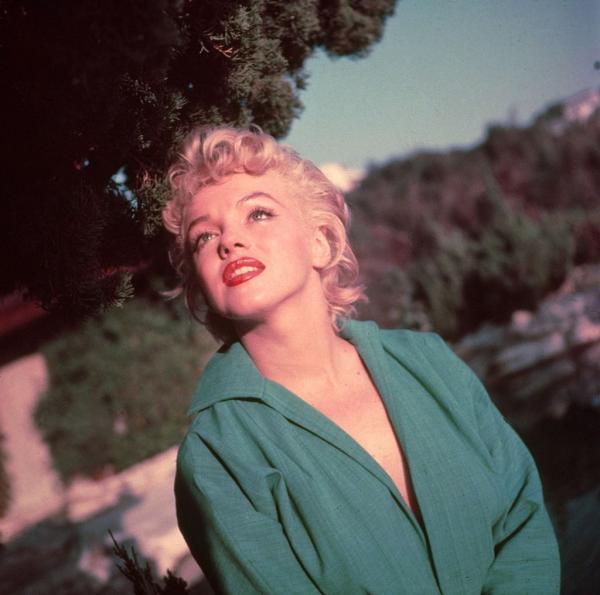 Marilyn Monroe, zâmbitoare, îmbrăcată într-o rochie verde