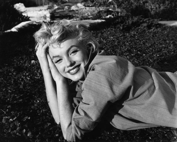 Marilyn Monroe, zâmbitoare, întinsă pe jos, fotografie alb negru