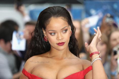 Rihanna, cu părul lung, desfăcut, îmbrăcată într-o rochie roșie, căzută pe umeri