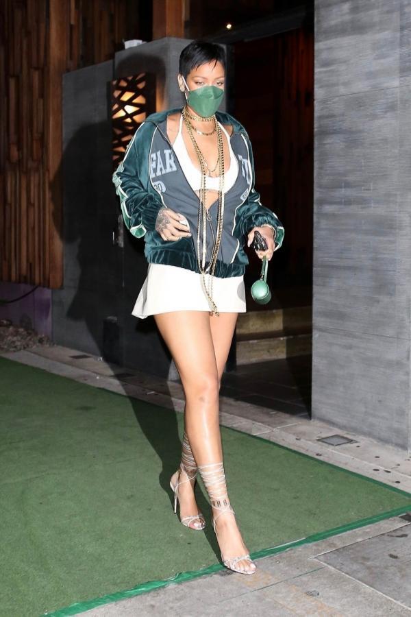 Rihanna este îmbrăcată în fustă mini albă și un top alb. Este tunsă scurt, pixie