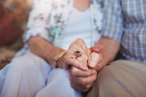 Bătrâni care se țin de mână, nu le vede fețele