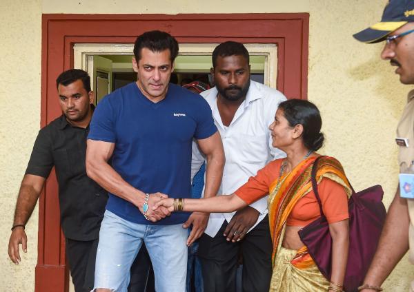 Salman Khan, îmbrăcat într-un tricou albastru, cu jeanși, salută apropiații.