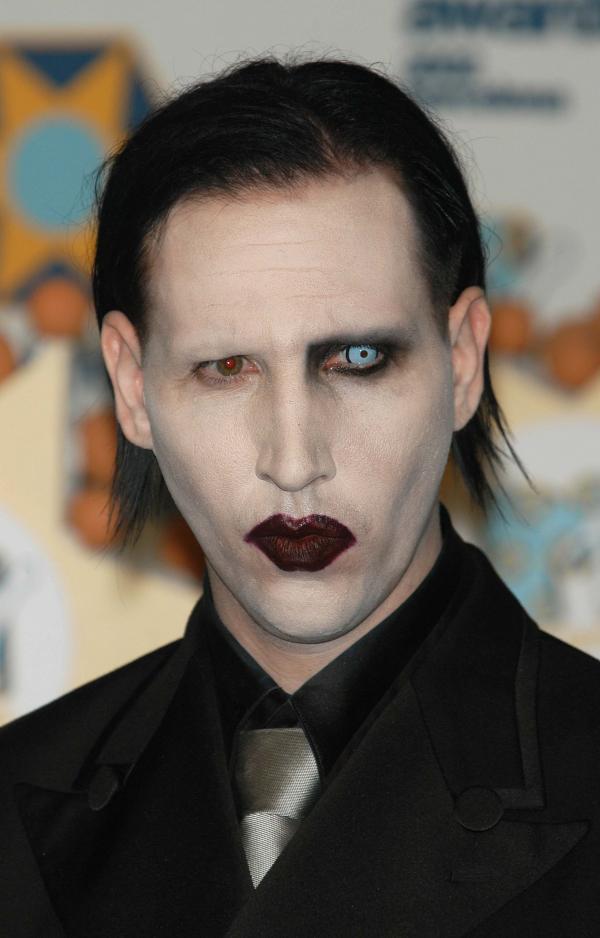 Marilyn Manson, îmbrăcat cu un costum negru, machiat strident, fotografiat la un eveniment muzical