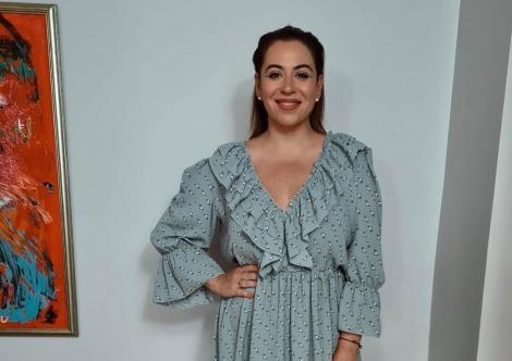 Oana Roman, îmbrăcată într-o rochie albastră, cu mână în șold