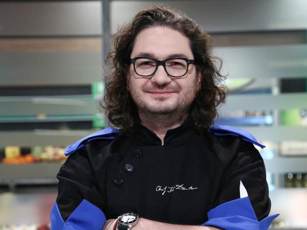 """Florin Dumitrescu, juratul emisiunii """"Chefi la cuțite"""", in bucatarie, imbracat cu tunica albastra"""