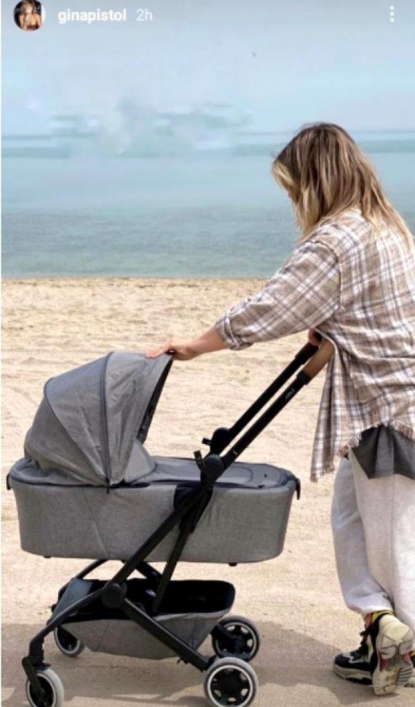 Gina Pistol, împingând căruțul cu micuța Josephine, la malul mării
