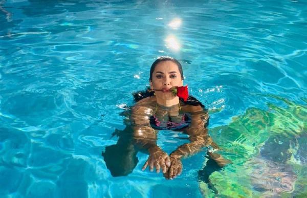 Oana Zăvoranu, în piscină, cu un trandafir în gură, în timpul filmărilor pentru serialul Sacrificiul