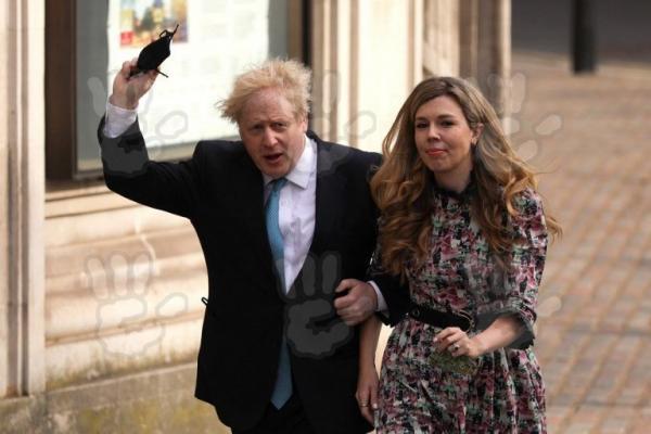 Boris Johnson, purtând sacou și cămașă și Carrie Symonds, într-o rochie înflorată