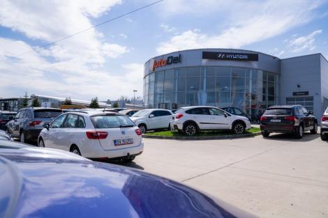 showroom-ul autodelrulate cu masini in parcare