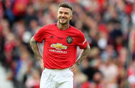David Beckham într-un tricou roșu și pantaloni scurți albi