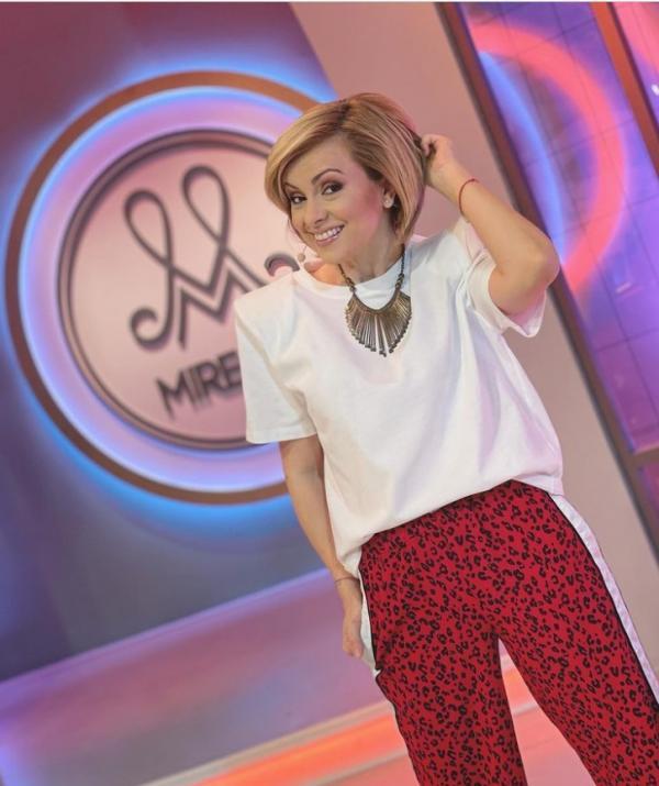 Simona Gherghe, în platoul emisiunii Mireasa, într-un triscou alb și pantaloni roșii