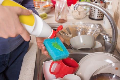 imagine cu mainile unei persoane cand spala vase cu detergent si burete