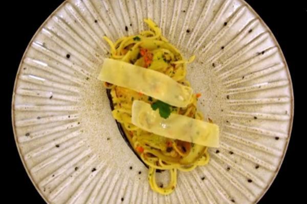Deasupra spaghetelor aglio olio cu peperoncino și vinete se așază felii subțiri de parmezan