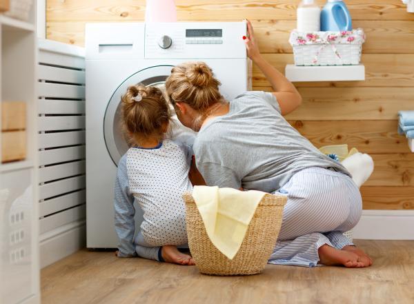 o femeie si o fetita se uita la masina de spalat haine