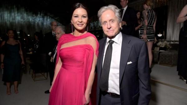 Catherine Zeta-Jones, îmbrăcată în rochie roz, lungă, și soțul ei, Michael Douglas, îmbrăcat la costum