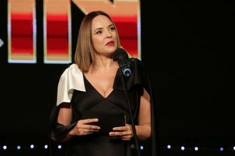 Andreea Marin, îmbrăcată într-o rochie elegantă, cu buzele roșii și păr desprins, la un eveniment public. Prezentatoarea TV vorbește la microfon