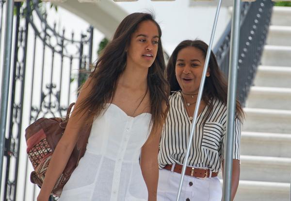 Sasha Obama și sora ei, Malia. Una dintre ele este îmbrăcată în rochie albă, cealaltă, în cămașă
