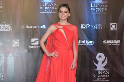 Daniela Aedo, îmbrăcată într-o rochie lungă, roșie, ține o mână în șold și zâmbește