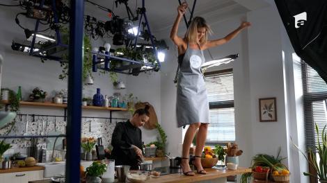 Roxana Blenche, la masa de gătit, și Ramona Olaru suită pe masă