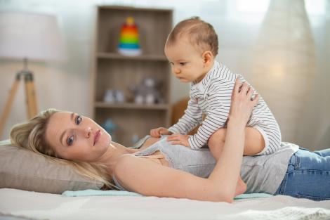 Un bebeluș și mama lui, într-un moment de tandrețe. Mama e întinsă și îl ține pe bebeluș pe burta ei