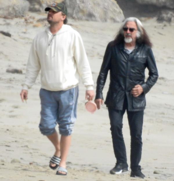 Leonardo DiCaprio, îmbrăcat într-un hanorac alb, alături de tatăl lui, pe plajă