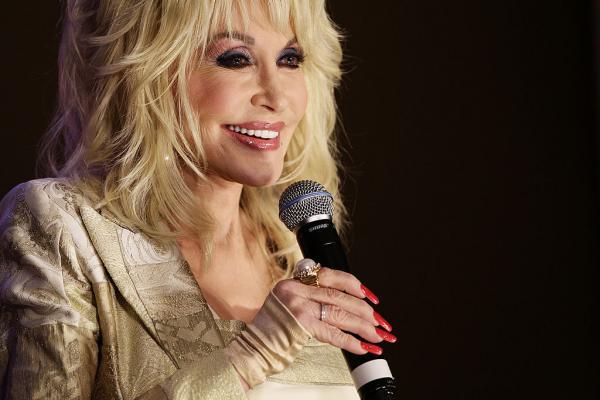 Dolly Parton, elegantă și frumos îmbrăcată, are un microfon în mână