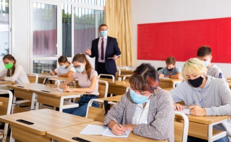 copii asezati in banci care sustin examenul la limba romana de la evaluarea nationala 2021