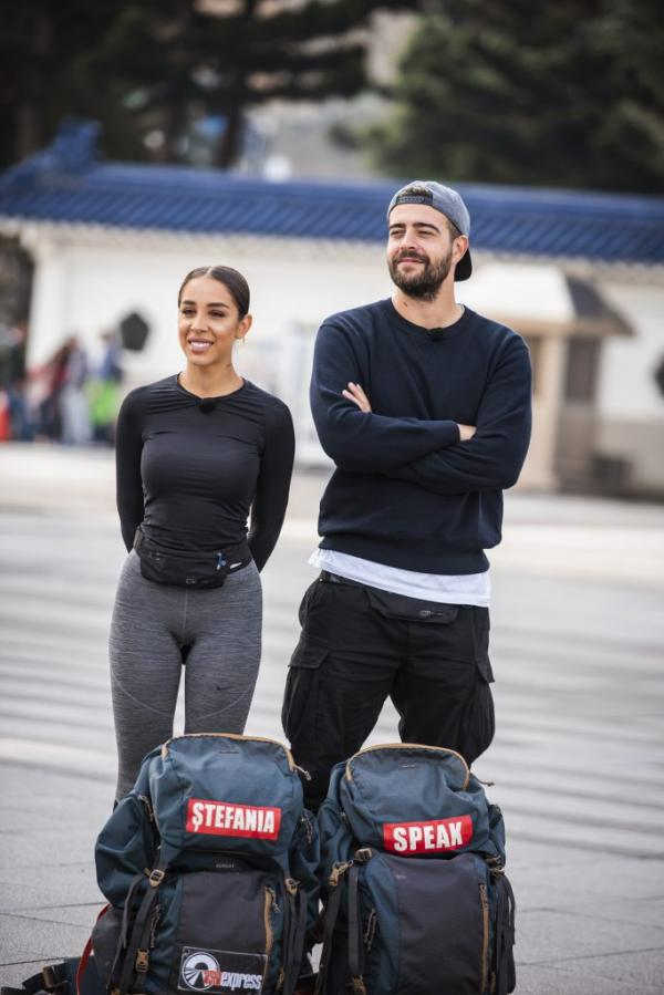 Speak și Ștefania în Asia Express, îmbrăcați în negru, lângă rucsacii lor din competiție