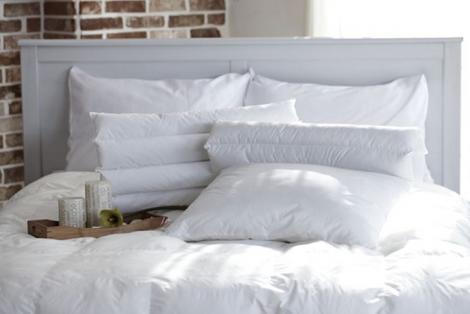 Un pat cu lenjerie albă și perne albe