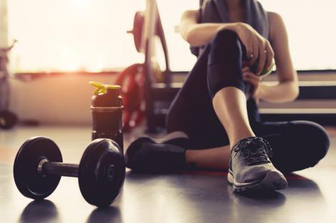 Fotografie făcută într-o sală de fitness, cu greutăți pe podea, și silueta unei femei