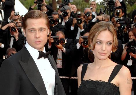 Angelina Jolie, cu părul prins, îmbrăcată într-o rochie neagră, și Brad Pitt, la costum negru cu papion