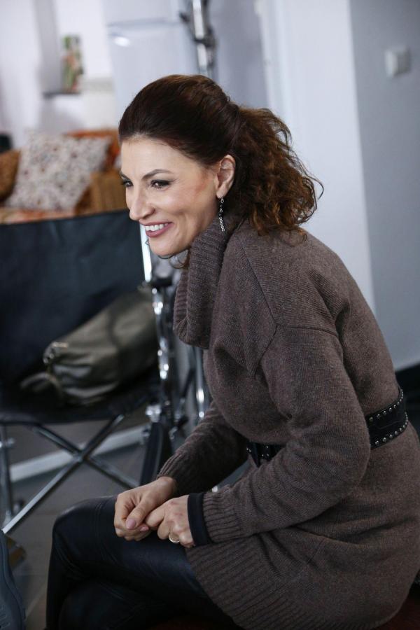 Ioana Ginghină, zâmbind, la filmările serialului Adela